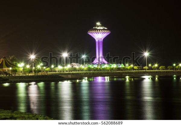 Water tower with reflection on water at night in Khobar in Saudi Arabia, a tower supporting an elevated water tank, whose height creates the pressure required to distribute the water through a piped