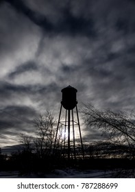 Water Tower Silhouette - Vertical image showing an old water tower in Newport Maine with the sun setting behind it and dark defined clouds overhead