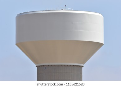 Water tower south of Dacono, CO, with watery blue sky and scattered clouds; close up of tank