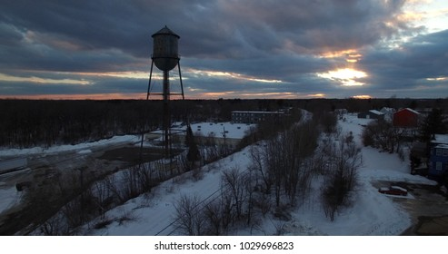water tower and sunset through the clouds