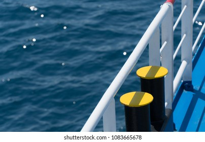 Water transportation concept, closeup on ship bollards with white railing and water in the background