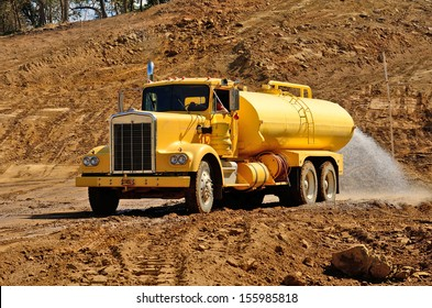 A water truck sprays water on a fresh fill layer of soil and rock for a new road construction project.