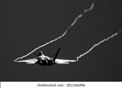 Water vapor trails from the wingtips of a fighter jet during an airshow demonstration.