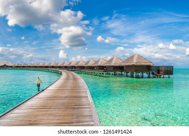 Water Villas (Bungalows) and wooden bridge at Tropical beach in the Maldives at summer day
