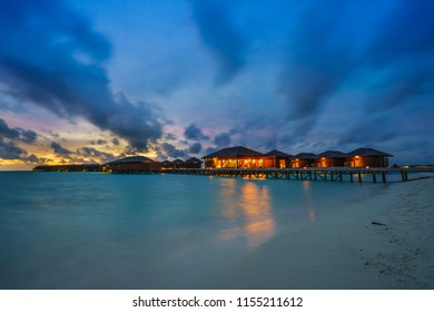 Water villas, Maldives resort island at twilight time