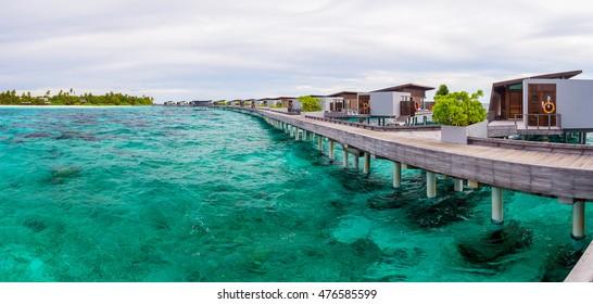 Water villas on tropical caribbean island, Maldives. Green blue ocean water.