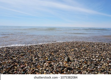 Water washing on shoreline over pebbles on beach on bright sunny day