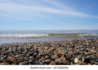 Water washing on shoreline over pebbles and beach with waves on lake on bright sunny day