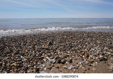 Water washing on shoreline over pebbles on beach on bright sunny day, blue sky in background