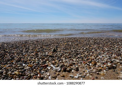 Water washing on shoreline over pebbles on beach on bright sunny day, horizon line in background.