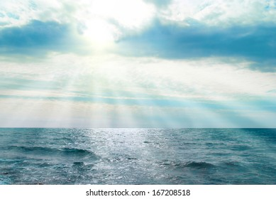 Water, waves and clouds. Sunset above the sea with sunbeams.