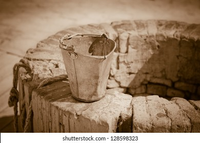 A water well with an old bucket. Vintage style photo.