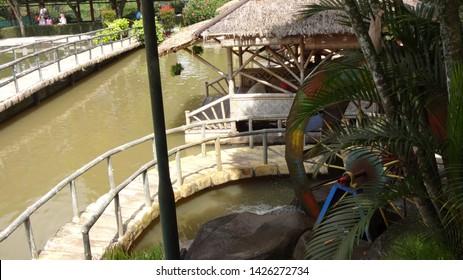 Water wheel next the fish pond at Nusantara Flower Garden in Cisarua, west java, indonesia. photo taken in june 2019