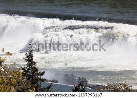 The water of the Willamette River cascading over Willamette Falls with birds in the mist on a spring day.