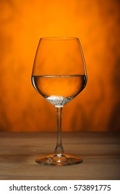 Water in a wine glass on the  orange background.
