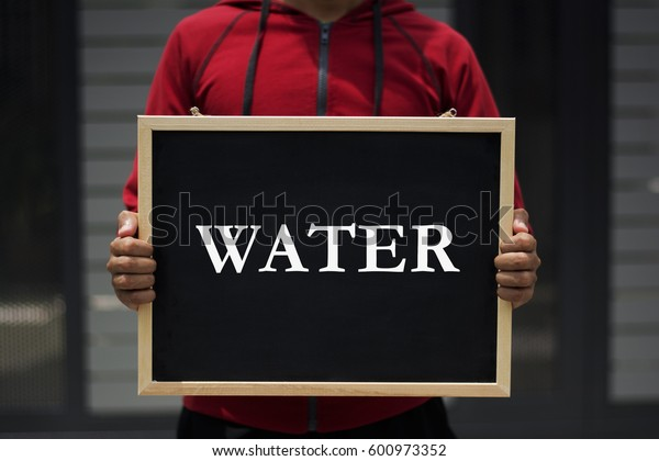 water written on blackboard with someone is holding it