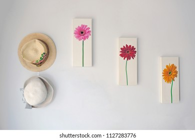 Watercolor art painting flower picture on frames with vintage hats hanging decorated and isolated on white concrete wall background