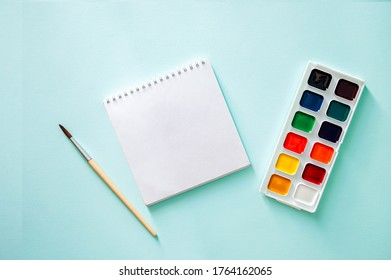 Watercolor paint , light beige brushes with brown pile and wooden texture and white clear sheet of note book on a light blue background. Horizontal photo. Flat lay minimalistic composition. Back to