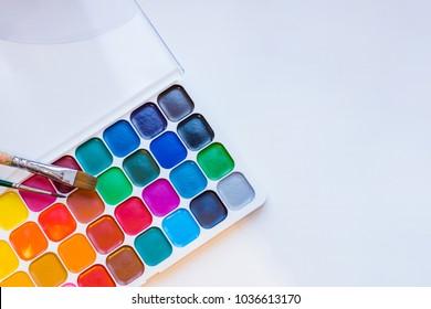 Watercolor paintbox. Color paints with paint brushes. Back to school concept. Kids painting concept. Children art. Top view. Copy space.