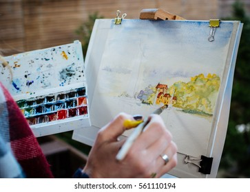 Watercolor painting with brush at the easel
