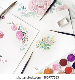 Watercolor painting and brushes at white background. Flat lay, top view