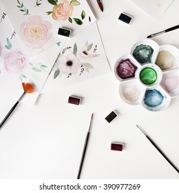 Watercolor painting and brushes at white background. Flat lay