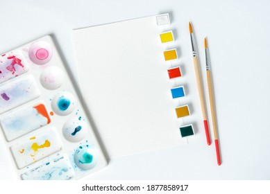 Watercolor paints in a box and brushes on a white background. Mockup for artists. Layout for designers