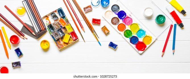 Watercolor paints with brushes and colored pencils on white wooden background, top view. Creative art concept