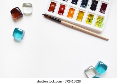 Watercolor paints and brushes, top view. Creative artistic mockup with copyspace