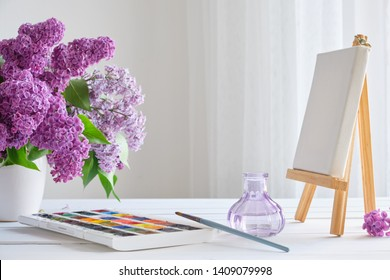 Watercolor paints, canvas on easel and lilac flowers bouquet on white table.