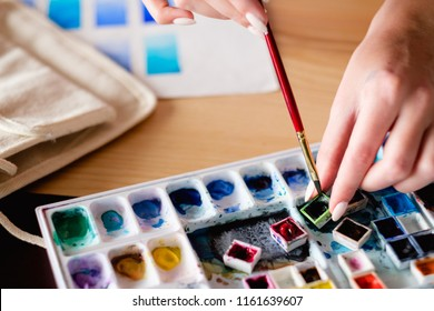 watercolor palette. artist tools instruments and inks for creative leisure. painting lessons concept. woman loading brush with color.