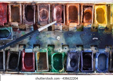 Watercolor palette with brush, old paint palette