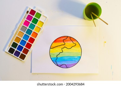Watercolor palette and paper with Drawn Earth painted with watercolors