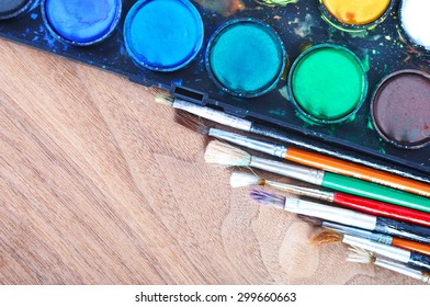 Watercolor palette with used brushes on a wooden table