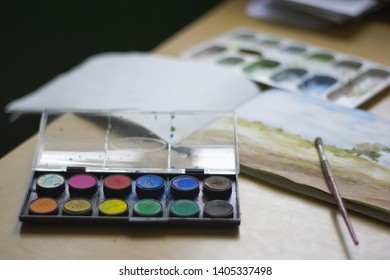 Watercolors with brush and sketchpad