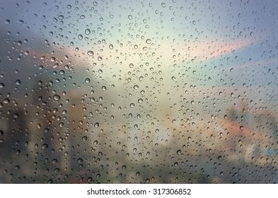 Waterdrops on a glass surface windows with cityscape background