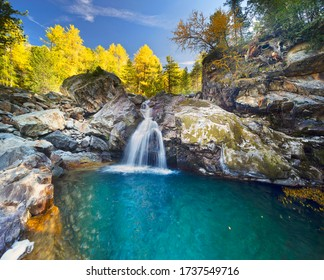 Waterfall in the Alps in the province of Morteratsch, near the famous railway. Autumn trees over the stormy water of a mountain river.