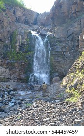 Waterfall among the rocks on the Putorana plateau. Mountain landscape in the North of Eastern Siberia.