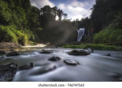 Waterfall in Bali in the morning breeze with sun rays