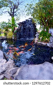 Waterfall and basin with colorful fish in the courtyard of the Wat Pho in Bangkok, Thailand