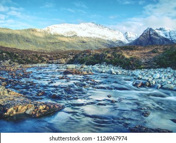 Waterfall between sharp exposed rocks, the Fairy pools on the Isle of Skye, Scotland. Trek by popular footpath by crystal clear blue pools on the River Brittle