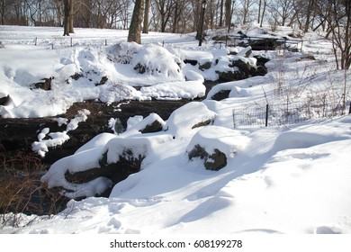 Waterfall between snow and fence in the park