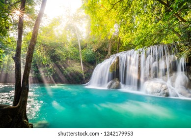 Waterfall and blue emerald water color in Erawan national park with sun light and light ray sunflare, Beautiful nature rock waterfall steps in tropical rainforest at Kanchanaburi province, Thailand