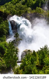 Waterfall Briksdal or Briksdalsbreen glacier in Olden, Norway and green mountains,