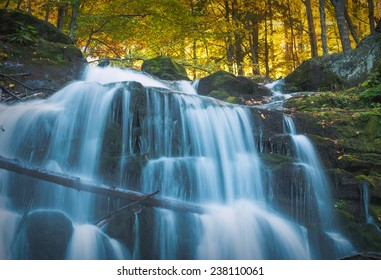 Waterfall in the Carpathian autumn forest. Blue clean water with motion blur