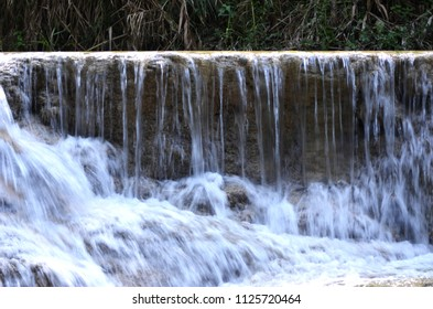 A waterfall of clear water is tumbling over brown rocks. A forest is behind.