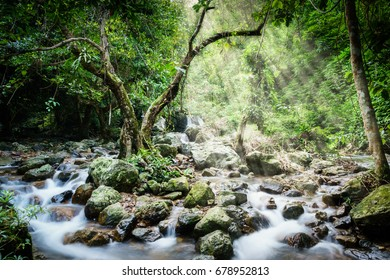 Waterfall in deep forest with light rays , Thailand