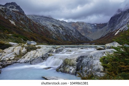 Waterfall of Esmeralda Lake, located in Patagonia Argentina. This place is surrounded by shrubs and turquoise water due to melting of a glacier. The background consists of mountains and clouds.