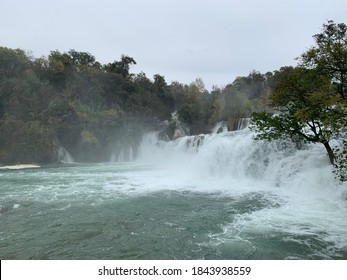 A waterfall and fall foliage in Krka National Park in Croatia, with green and yellow trees.