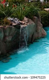 waterfall falling in a blue lagoon swimming pool